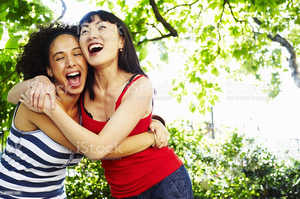 Two women embracing and laughing royalty free stockfoto