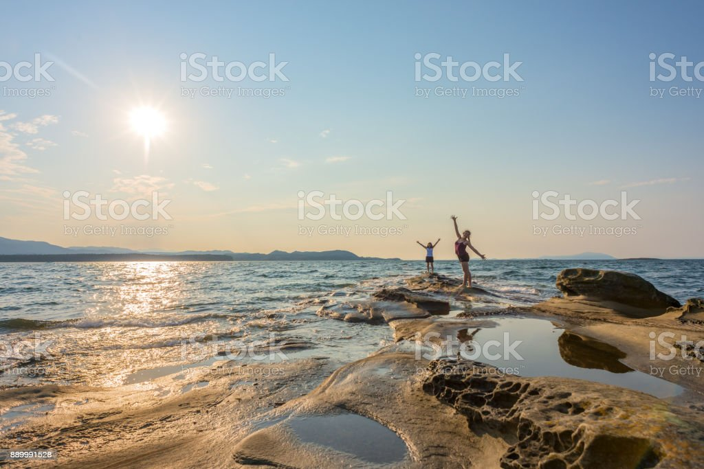 Two Women Embracing Nature with Arms Outsretched on Remote Beach stock photo