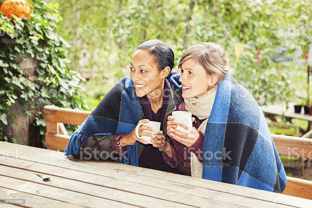 Two women enjoy a hot beverage royalty-free stock photo