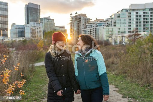 Two women are enjoying time together outdoors. They are holding hands and walking on a dirt path through a park near the city. It is cool outside and the smiling women are wearing jackets. The sun is setting behind them. Skyscrapers are visible in the background.