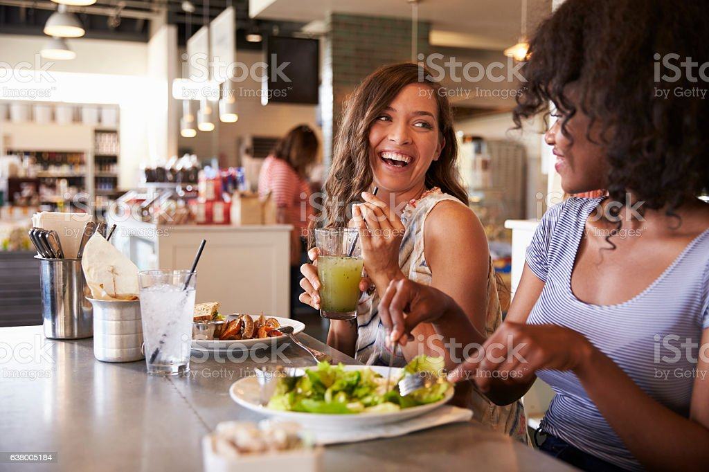 Two Women Enjoying Lunch Date In Delicatessen Restaurant - foto de acervo