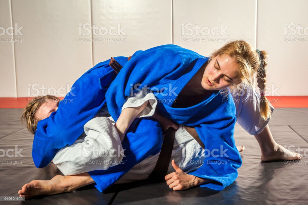 Two women fight judo on tatami stock photo