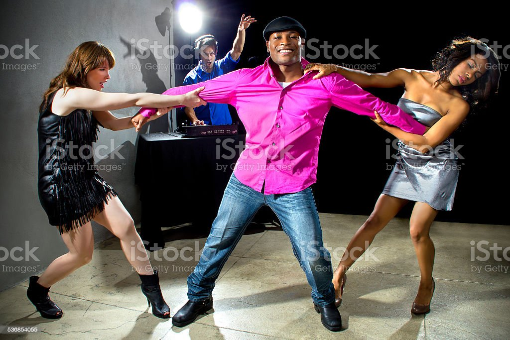Two Women Fighting Over a Man in a Nightclub stock photo