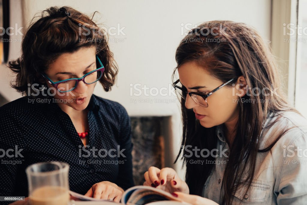 Two women flipping through a book in a coffee shop foto stock royalty-free