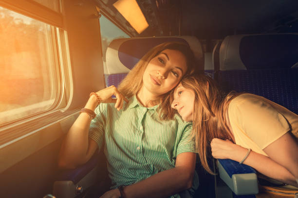 Two women Friends looking at sunset while traveling by train. Candid authentic moment stock photo