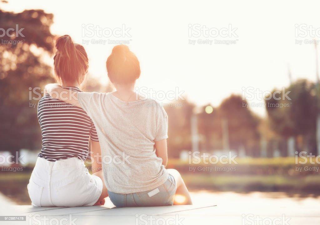 Zwei Freundinnen ruht im Garten, beobachten die Sonne zusammen glücklich. – Foto
