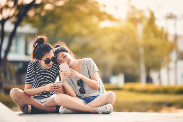 two women friends sit in the park and relax on a happy holiday. - kids phones stock photos and pictures