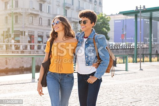 Two friends having a casual chat while walking on street. Two multiethnic girls laughing and walking in the city centre. Brazilian young woman and stylish latin girl wearing sunglasses and staying together oudoors.