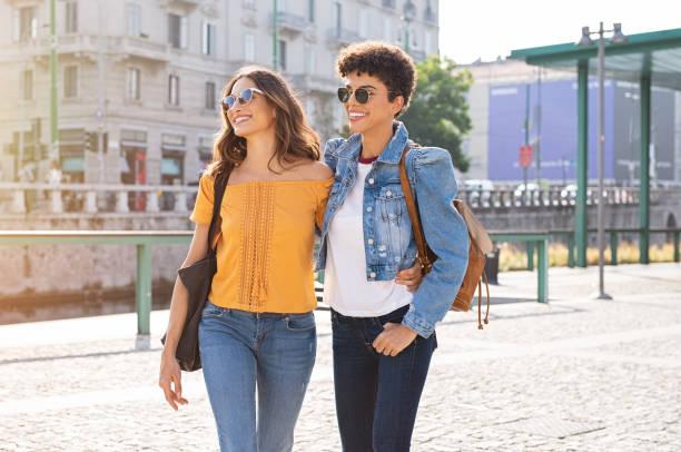 Two women friends walking on street - fotografia de stock