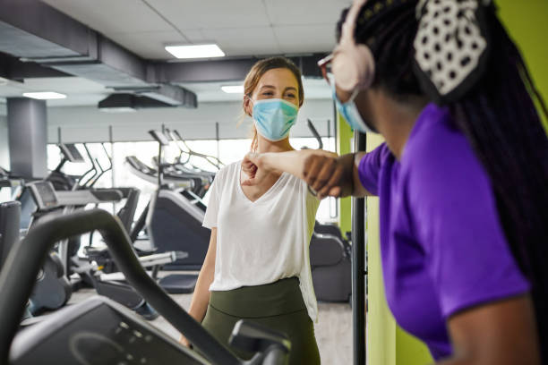 Two Women Greeting With Elbow Bump In The Gym During Coronavirus Pandemic stock photo
