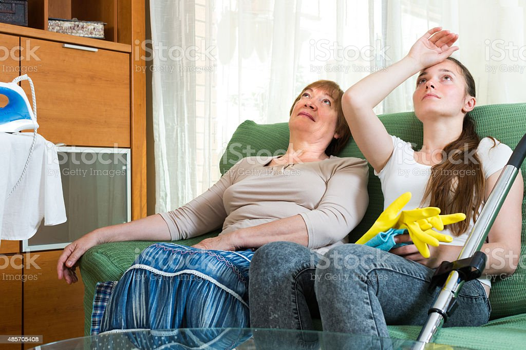 Two women having a rest after cleaning stock photo