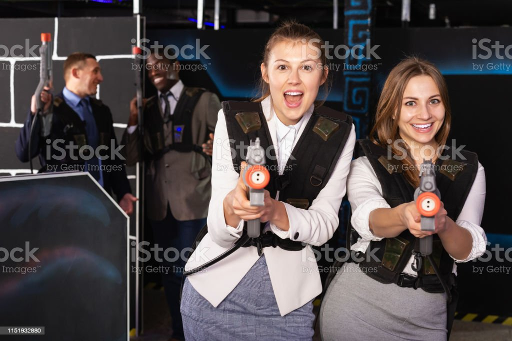 Two happy women having corporative entertainment in laser tag room