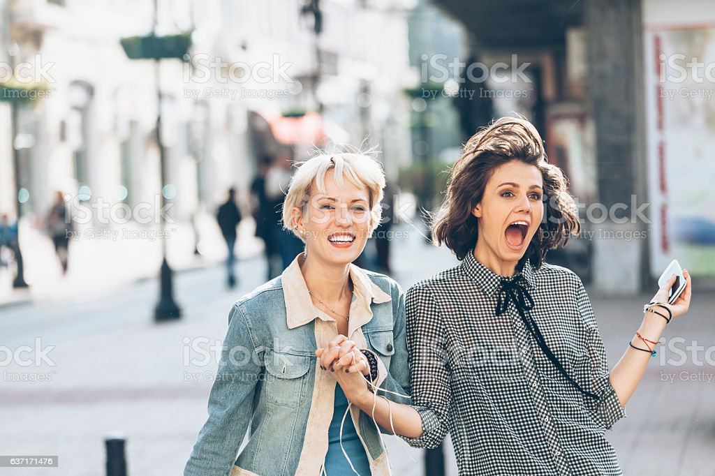 Two women having fun on street - Photo
