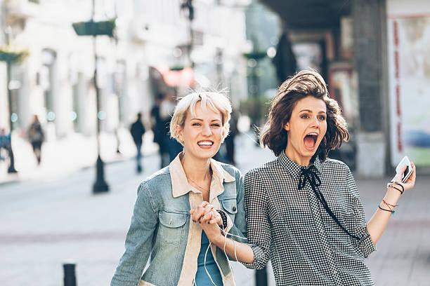 Two women having fun on street - Photo