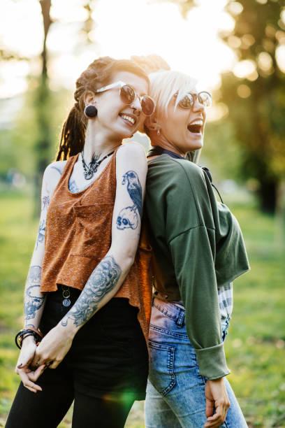 zwei frauen spaß zusammen im park am sonnigen sommertag - freundin tattoos stock-fotos und bilder