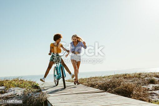 Two young women having fun with a bicycle at the beach. Woman running with friend riding a bike on boardwalk.