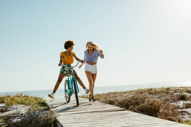 Two women having fun with a bicycle at beach Two young women having fun with a bicycle at the beach. Woman running with friend riding a bike on boardwalk. boardwalk stock pictures, royalty-free photos & images
