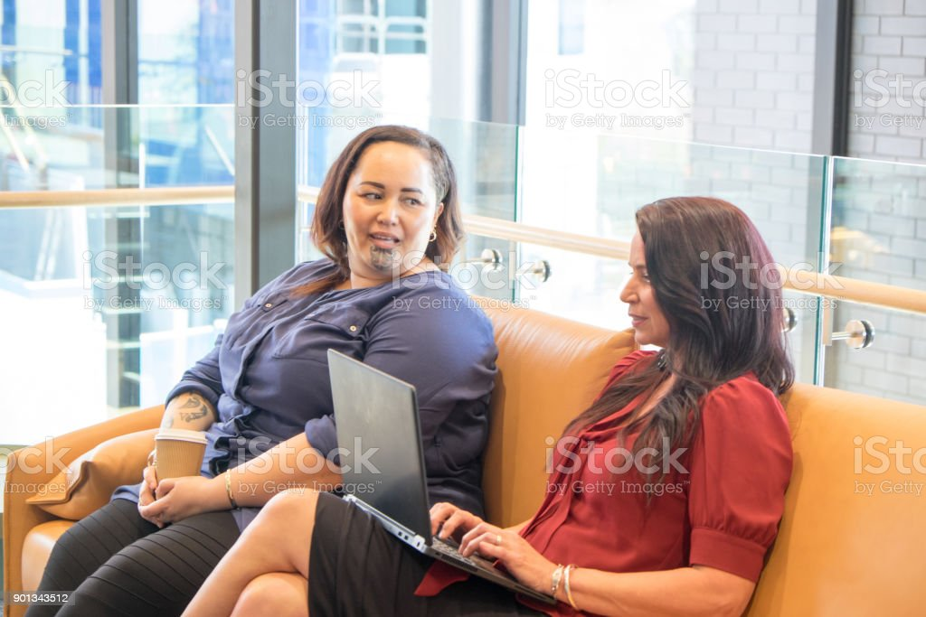 Two women having informal meeting on couch; caucasian female is working on laptop computer; Maori employee has tattoos including facial to moko. stock photo