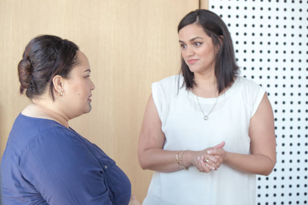 Two women having serious conversation - could be friends or work colleagues. Focus is on plus size female on left. Females are of maori ethnicity. stock photo