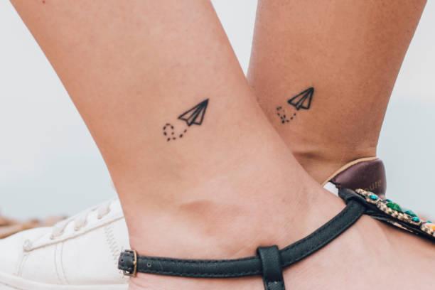 zwei frauen, die das gleiche tattoo - freundin tattoos stock-fotos und bilder