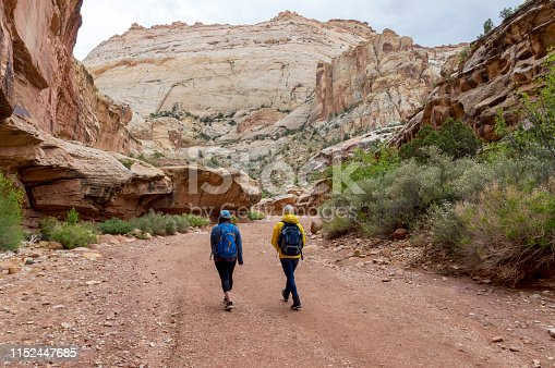This view shows the Grand Wash area in Capitol Reef National Park.  Two women are hiking on the trail surrounded by the steep canyon walls around them.