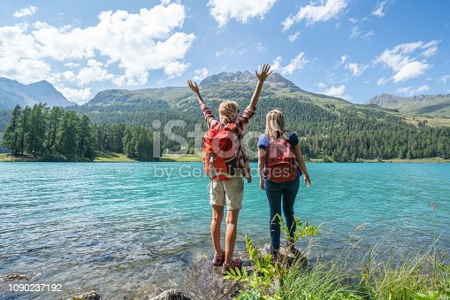 Two women hiking stand by a mountain lake contemplating the beautiful nature, one girl arms outstretched for freedom and positivity- Shot in Switzerland