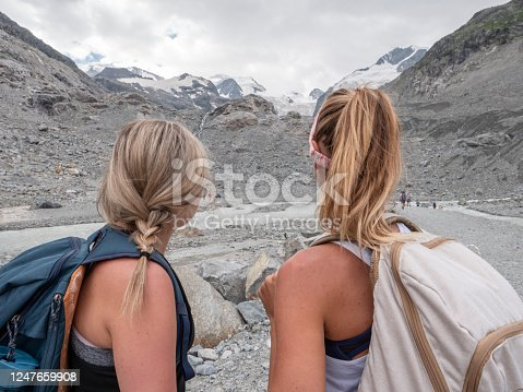 Two women hiking together in Summer exploring glacier area in the high mountains in the Alps. People travel nature outdoor activities