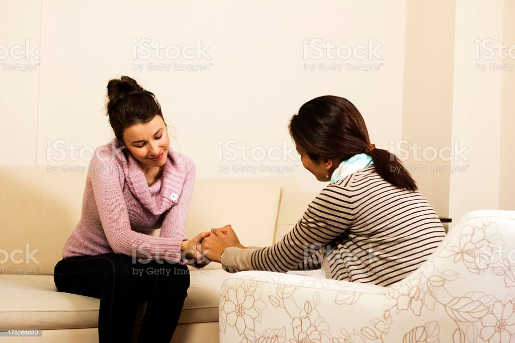 Two women holding hands and sitting across from each other stock photo