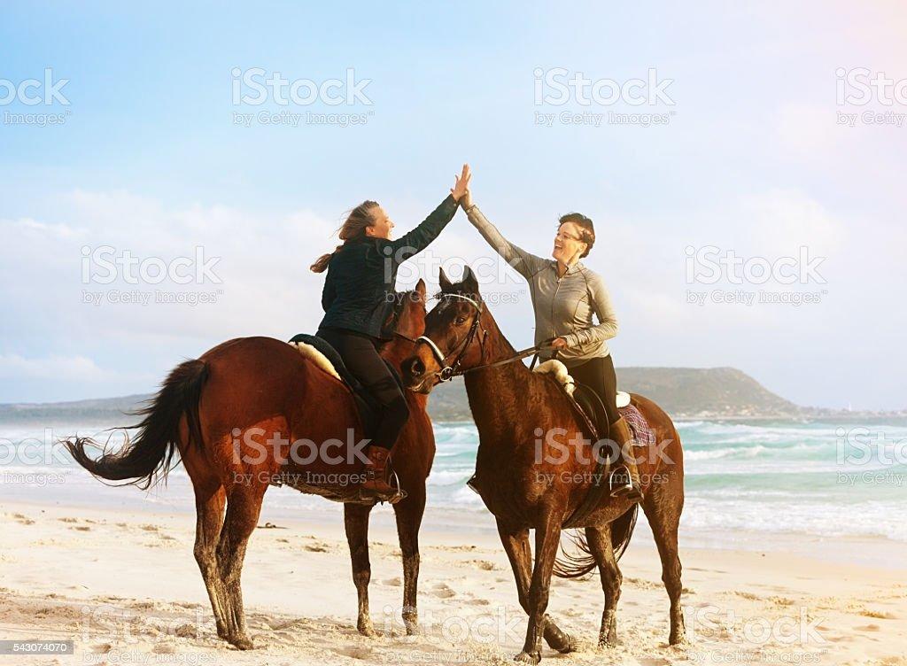 Two women horse riders greet each other on idyllic beach stock photo