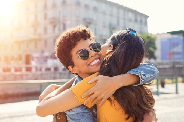 dwie kobiety przytulające się na placu miejskim - przyjaźń zdjęcia i obrazy z banku zdjęć