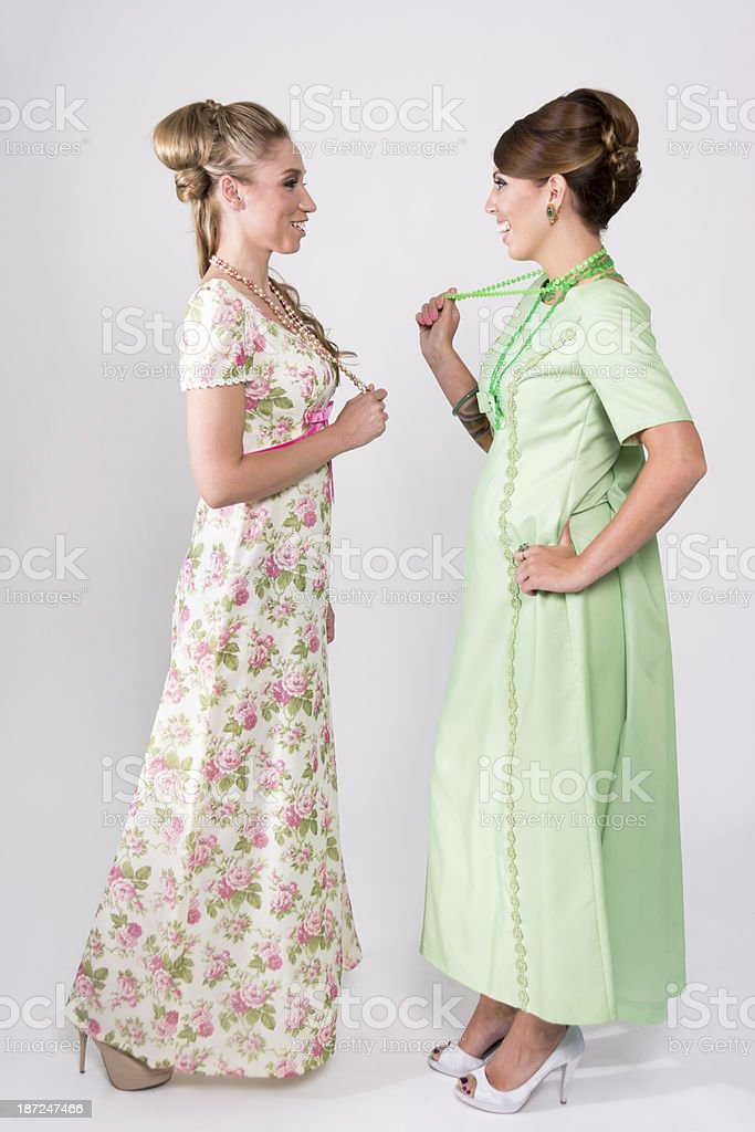 Two women in 60s style long dresses, chatting. stock photo