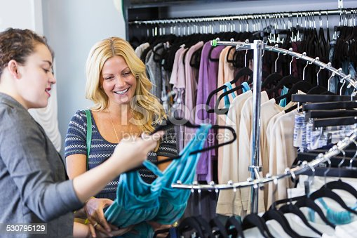 istock Two women in a clohting store looking at a dress 530795129
