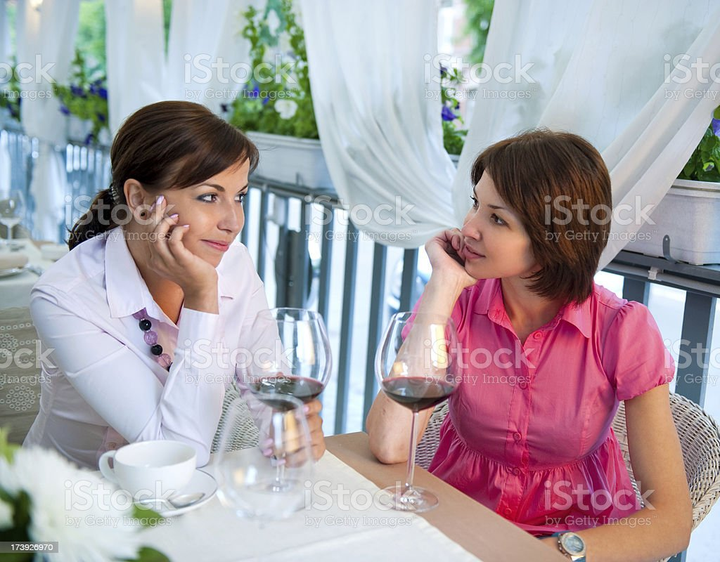Two women in a restaurant drinking red wine royalty-free stock photo