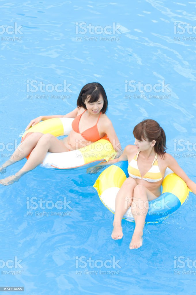 Two women in bathing suits floating in inner tubes royalty-free stock photo