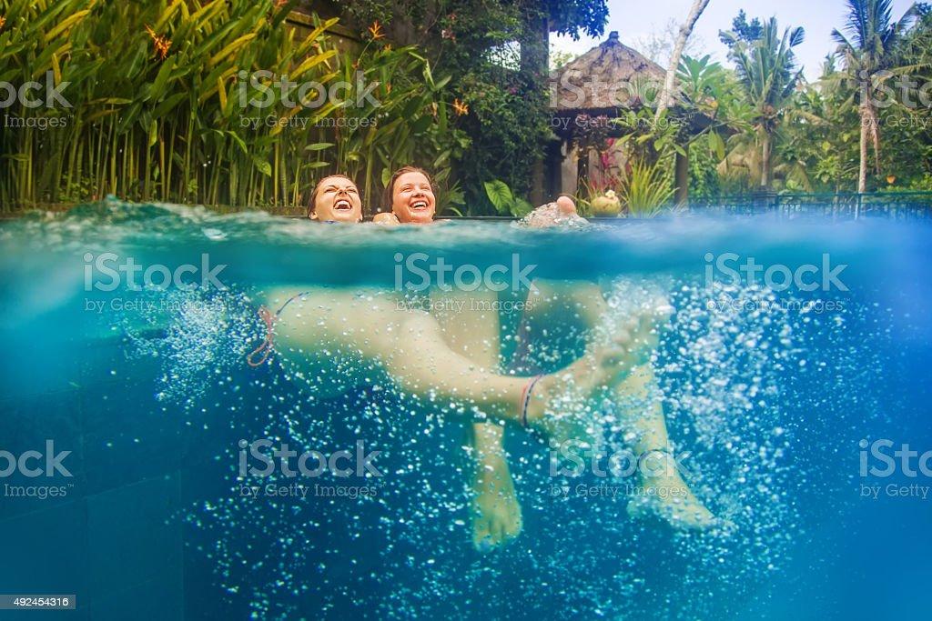 Two women in bikini relaxing in a tropical swimming pool stock photo