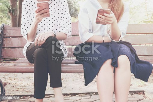 istock Two women in disinterest moment with smart phones in the outdoor, concept of relationship apathy and using new technology and smartphone addiction. vintage tone 646552328