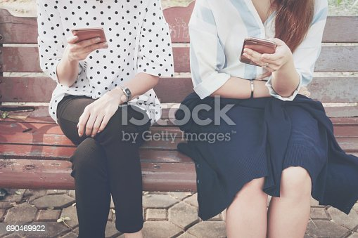 istock Two women in disinterest moment with smart phones in the outdoor, concept of relationship apathy and using new technology and smartphone addiction. vintage tone 690469922