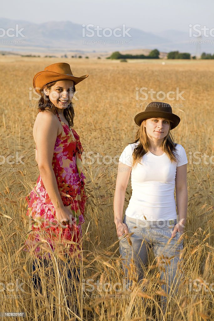 Two women in golden wheat field royalty-free stock photo