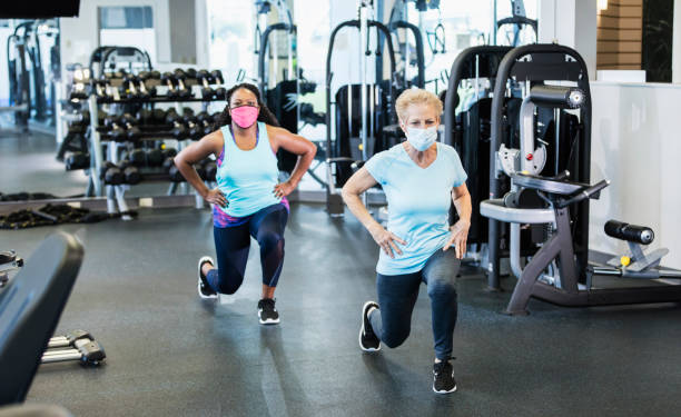 Two women in gym exercising, wearing face masks. stock photo