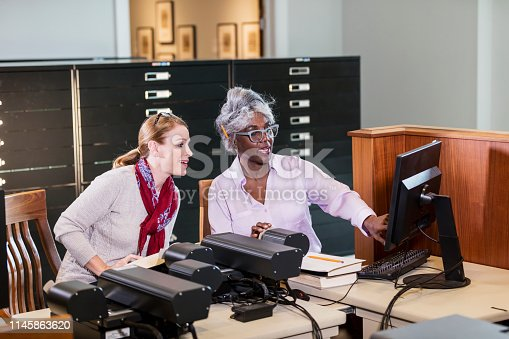 Two multi-ethnic women working together in the library. They are sitting at a computer attached to microfiche readers, doing research, reviewing old documents stored on the microfiche.