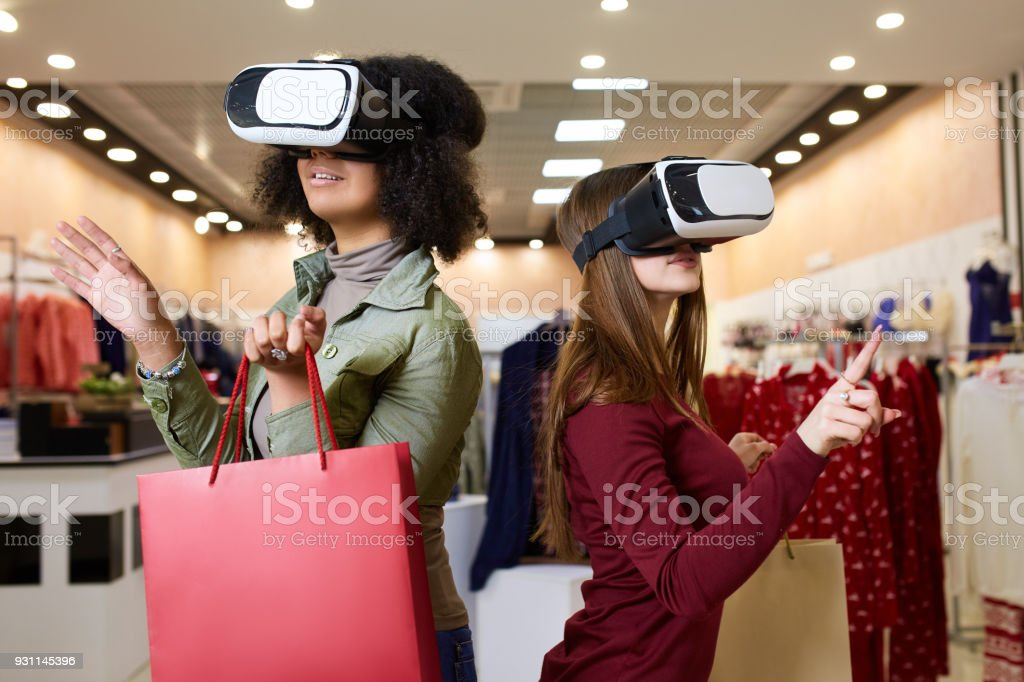 Two women in modern virtual reality headsets having expirience in shopping at lingerie store. Multiracial girls in vr glasses with bags touching and pointing interface elements in underwear shop stock photo