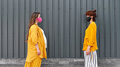 istock Two women in protective masks and yellow clothes stand in the distance. The concept of social distance. 1225599382