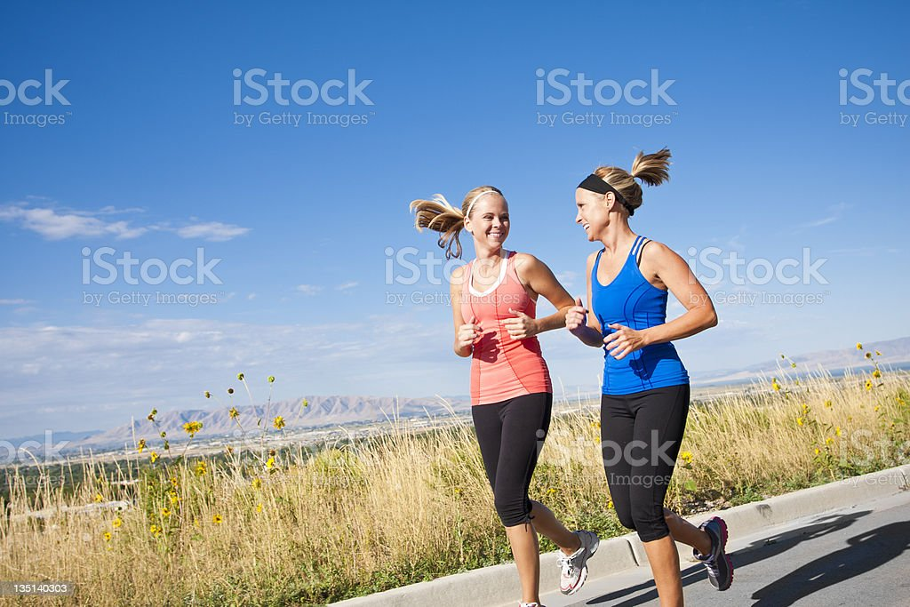 Two women jogging and conversing by the mountains stock photo