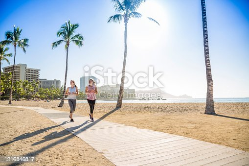 Two Women jogging on the beach boardwalk between two palm trees. Great fitness photo of women working out. Copy space in the blue sky and sand
