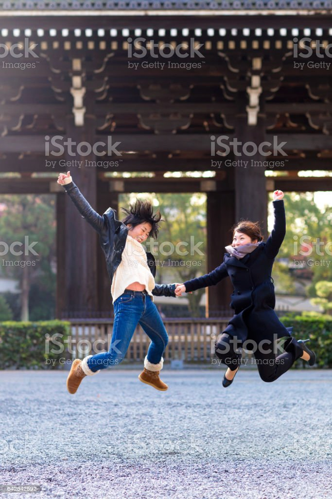 Two women jumping in excitement at a Japanese temple in Kyoto, Japan stock photo