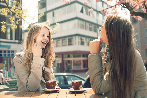 Two women laughing together while drinking coffee at a cafe stock photo