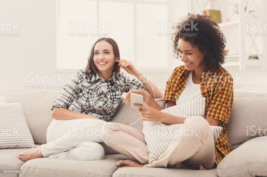 Two women listening music and sharing earphones stock photo