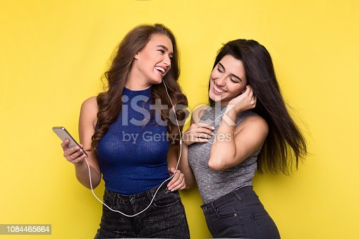 istock Two women listening music online on smartphone 1084465664