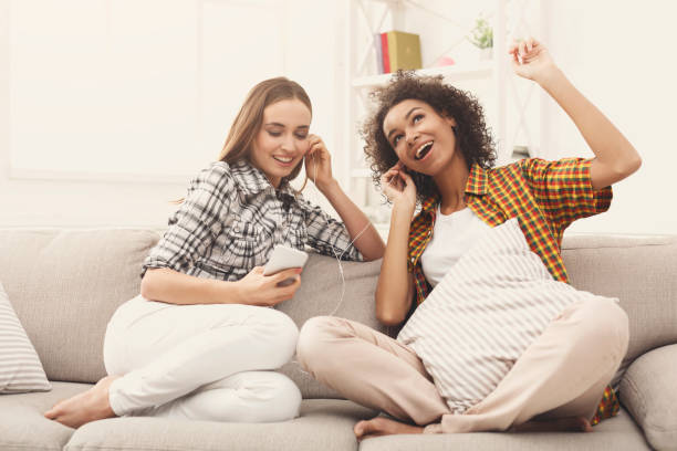 Two women listening to music and sharing earphones stock photo