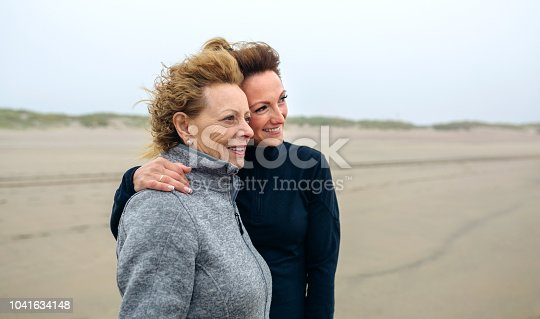 Two women looking at sea on the beach in autumn